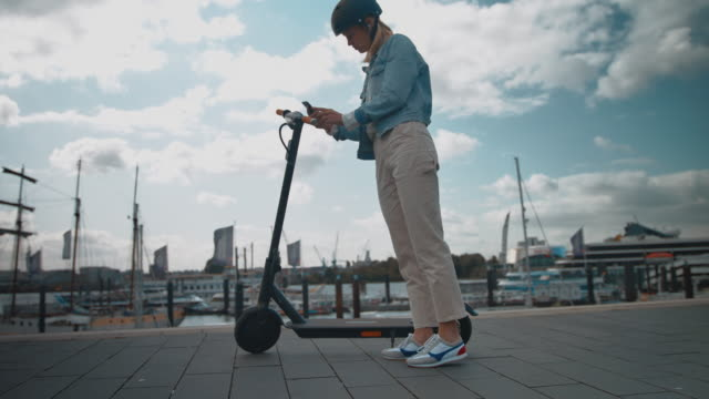 woman unlocking electric scooter with mobile phone - monopattino elettrico video stock e b–roll
