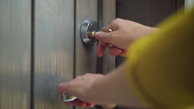 Woman unlocking entrance door with a key. Person using key and locking door. Real estate security concept