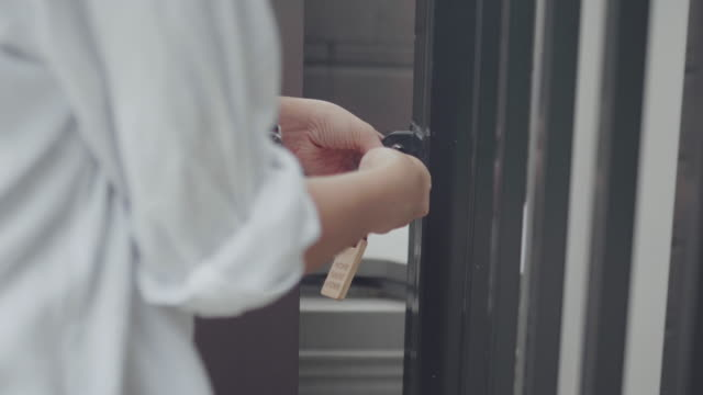 Woman unlocking entrance door with a key. Person using key and locking door. Real estate security