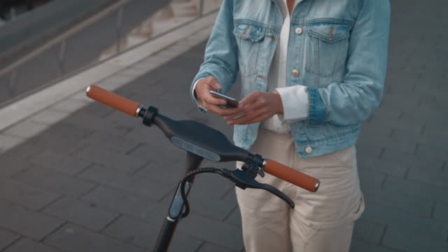 woman unlocking push scooter with mobile phone - monopattino elettrico video stock e b–roll