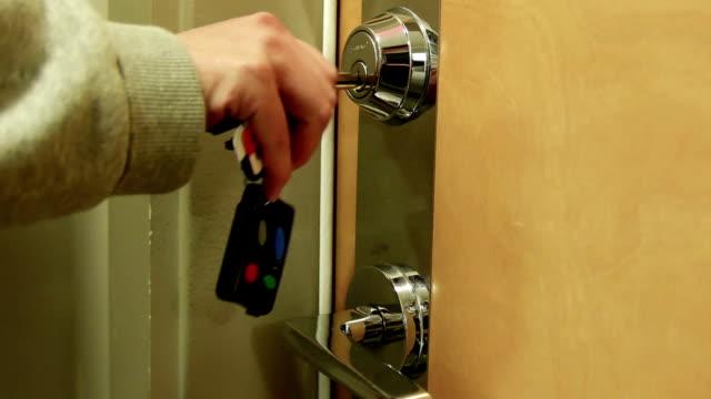 vídeos de stock e filmes b-roll de mulher destranca um porta da casa - chave