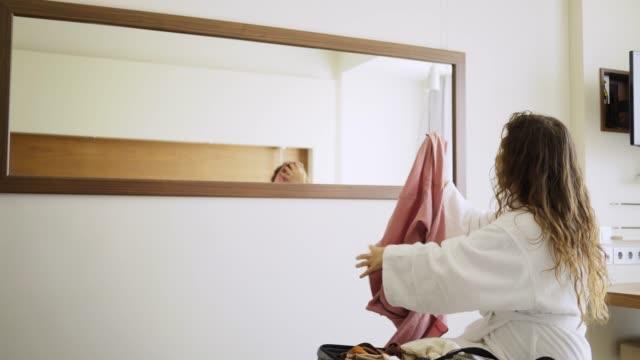 Woman unpack suitcase in bedroom