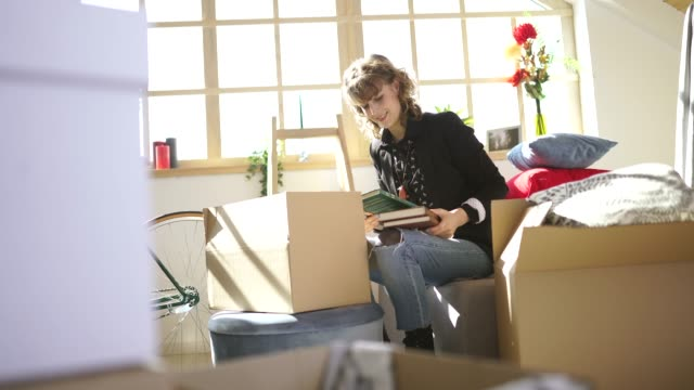 Woman unpacking boxes at new apartment