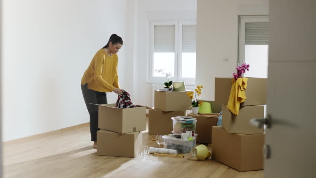 Déballage des boîtes en carton dans son nouvel appartement de femme - Vidéo