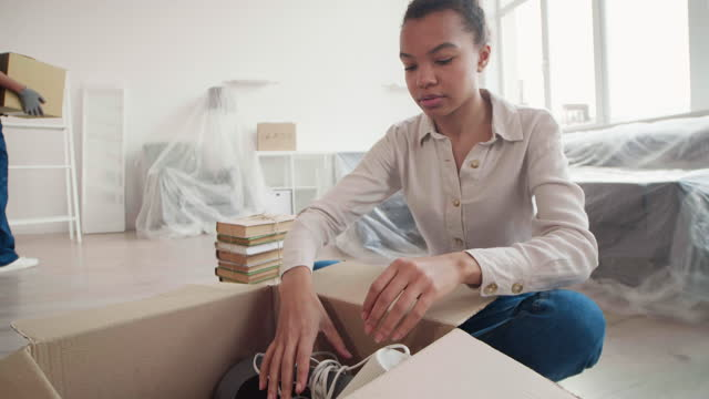 Woman Unpacking Her Stuff while Worker Carrying Boxes
