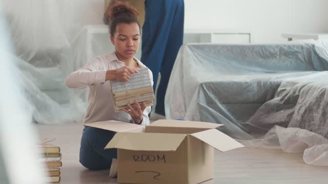 Woman Unpacking in New House while Worker Carrying Boxes