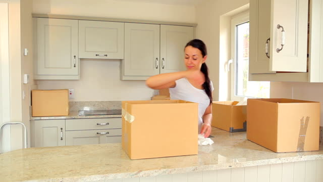 Woman unpacking moving boxes video