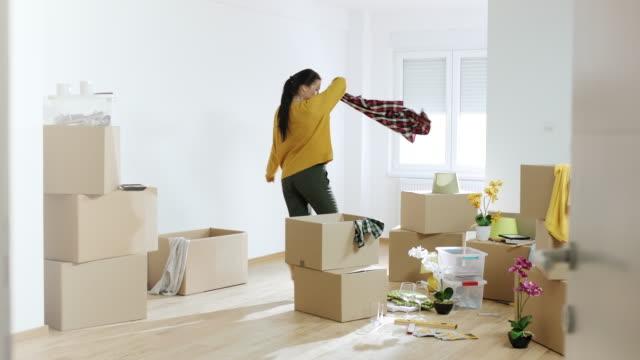 kvinna uppackning saker från lådor och dans i sitt nya hem - flyttlådor bildbanksvideor och videomaterial från bakom kulisserna