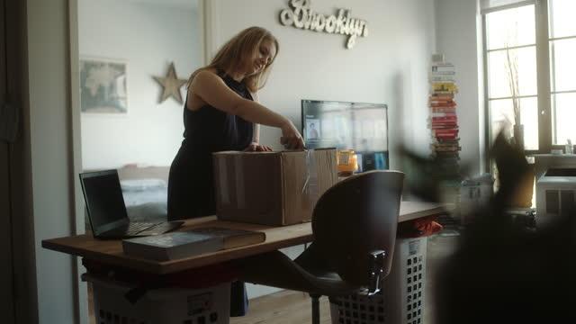la donna disfa la consegna a domicilio nell'appartamento loft. - etnia video stock e b–roll