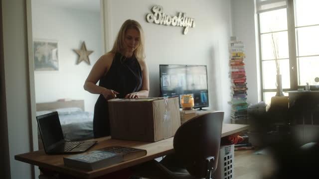 kobieta rozpakowuje dostawę do domu w mieszkaniu na poddaszu. - paczka sukienka filmów i materiałów b-roll