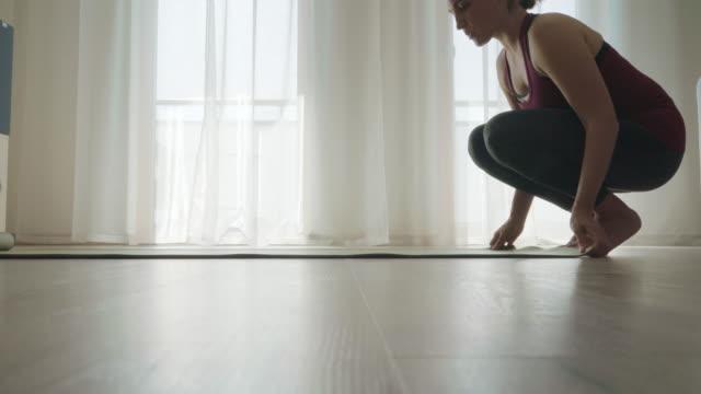 4k donna srotolare tappetino yoga prima di fare esercizi sul pavimento a casa accovacciato - materassino ginnico video stock e b–roll