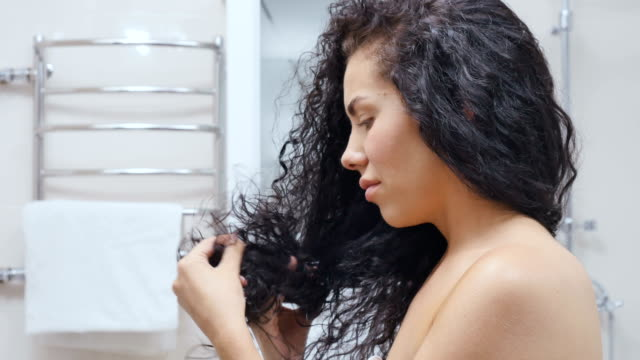woman upset because of her damaged hair - capelli ricci video stock e b–roll