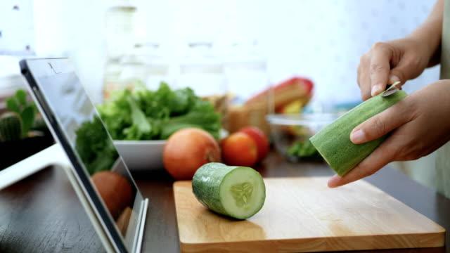 vidéos et rushes de 4 k. femme utiliser glissement de doigt sur l'écran de la tablette et éplucher un concombre, préparer les ingrédients pour la cuisson suivre clip vidéo en ligne sur le site web par l'intermédiaire de tablette de cuisine. contenu sur la technologi - recette