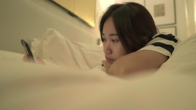 携帯電話の女性の使用と夜にベッドの上に横たわっている - 女性 落ち込む点の映像素材/bロール