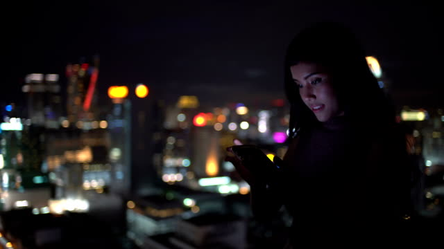 Woman use smartphone very happy for communicate including connection her friend ,watching funny video,email, chat and shopping online in city at night : Gimbal shot - vídeo