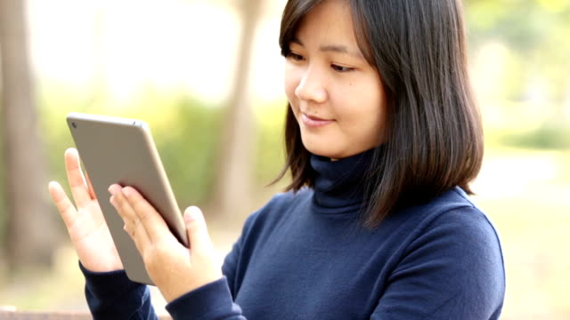 Woman use Tablet at Nature park