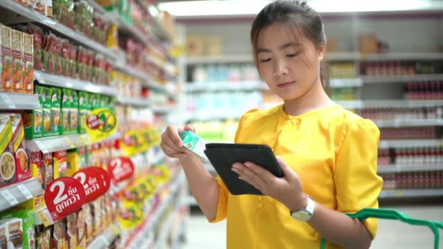 stockvideo's en b-roll-footage met de tablet van de gebruik van de vrouw bij winkelcentrum - discountwinkel