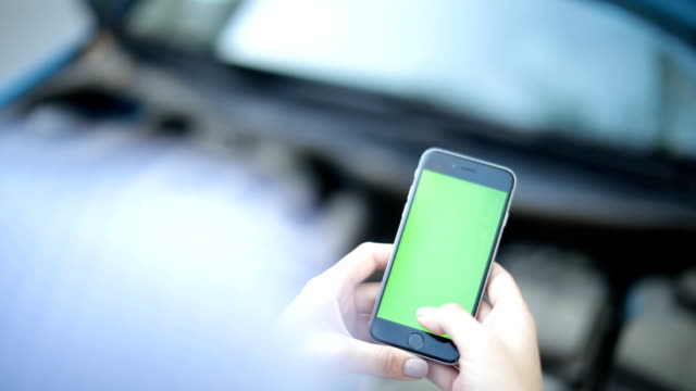 Woman uses a phone with a green background video