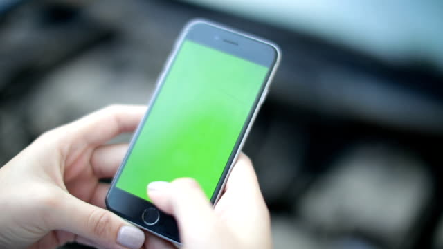 Mujer utiliza un teléfono con un fondo verde - vídeo