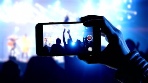 donna usa uno smartphone in un concerto musicale per registrare video dell'evento - filmare video stock e b–roll