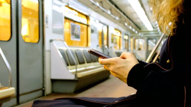 vidéos et rushes de femme utilise un smartphone dans le gros plan de métro - wagon