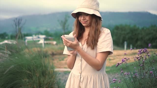 woman uses a smartphone to shoot flowers.
