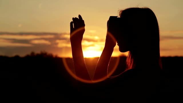 женщина использует виртуальная реальность очки в лесу на закате - google стоковые видео и кадры b-roll