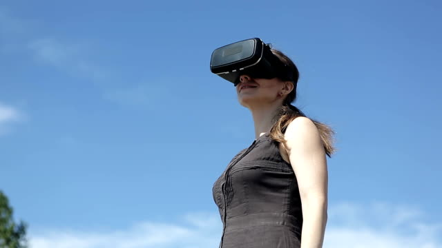 woman uses a virtual reality glasses on the backfound of sky video