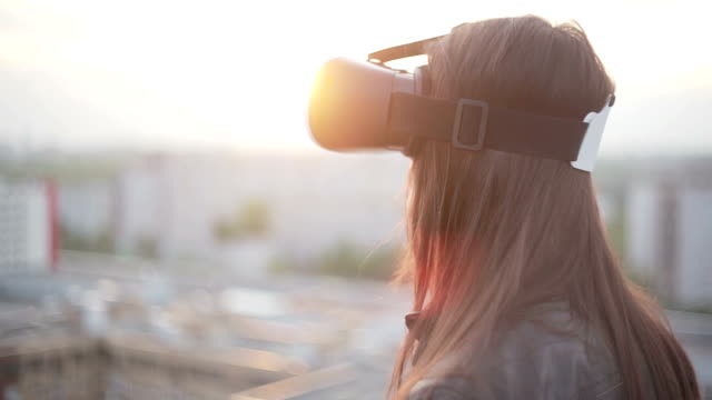 woman uses a virtual reality glasses on the roof video