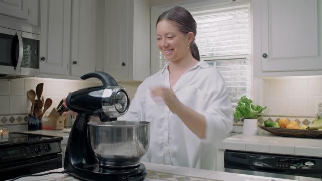 vidéos et rushes de la femme emploie un mélangeur électrique dans sa cuisine - batteur électrique