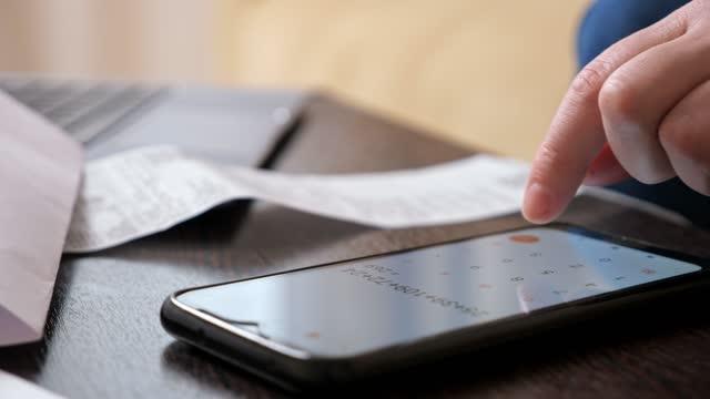 vídeos de stock, filmes e b-roll de mulher usa calculadora no celular para contar grandes pagamentos - alto descrição geral