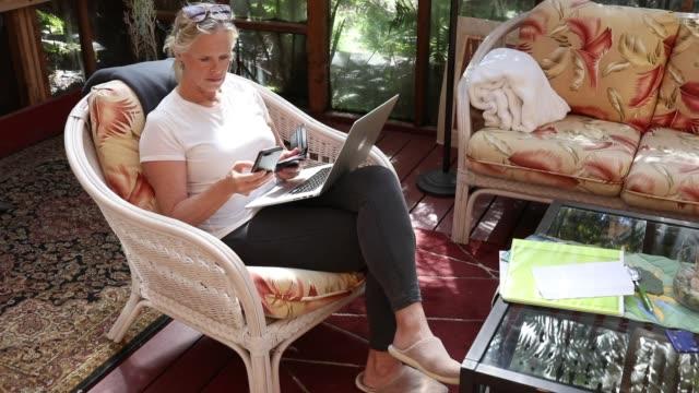 kvinnan använder dator och telefon medan online shopping - byxor bildbanksvideor och videomaterial från bakom kulisserna