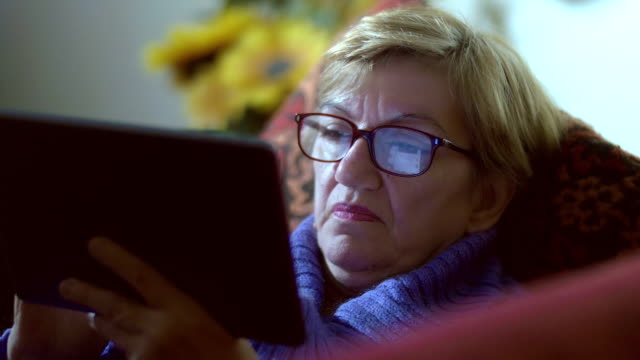 woman uses facebook on tablet: reflection on her glasses video