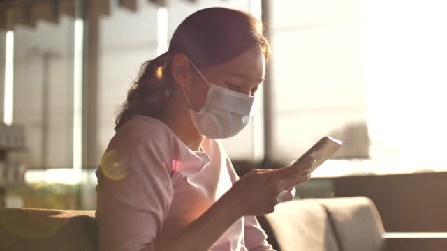 Woman uses smart phone with a protective face mask