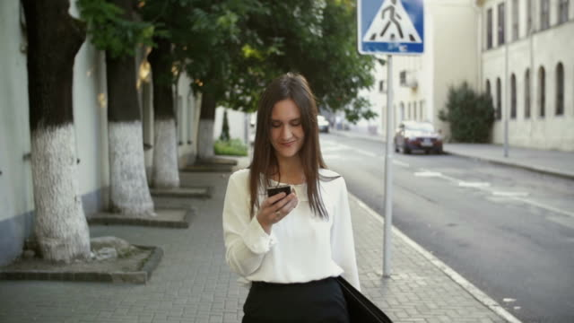 Woman uses smartphone walking in old city. slow mo video