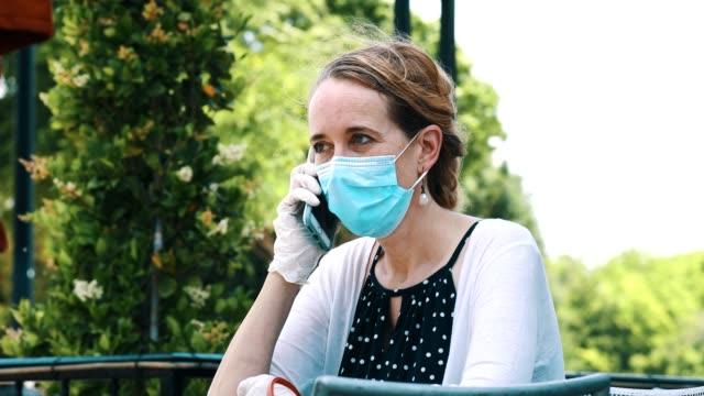 frau nutzt smartphone im freien während covid-19-pandemie - smartphone mit corona app stock-videos und b-roll-filmmaterial