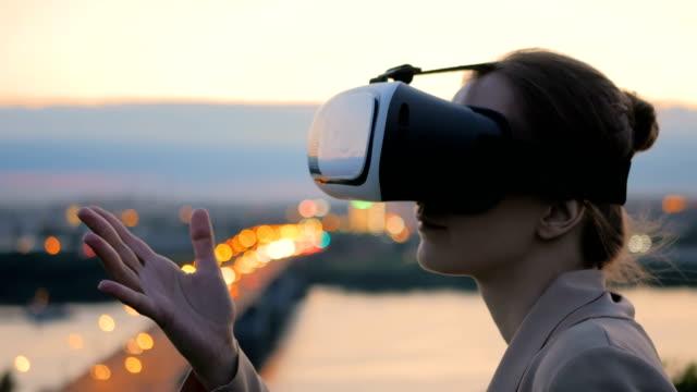 vídeos de stock, filmes e b-roll de mulher usa óculos de realidade virtual na cidade após o pôr do sol - realidade virtual