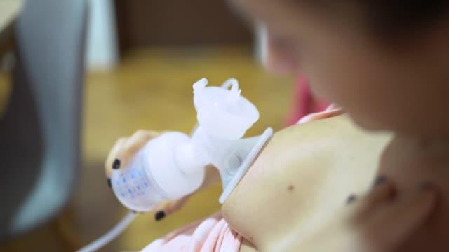 kvinna med hjälp av en bröstpump - värmepump bildbanksvideor och videomaterial från bakom kulisserna