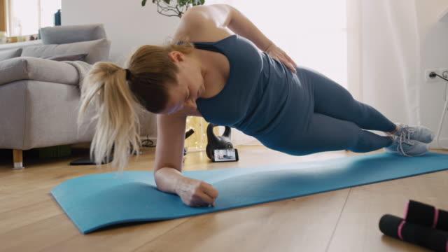 vídeos de stock e filmes b-roll de slo mo woman using a mobile phone for an online exercise training - treino em casa