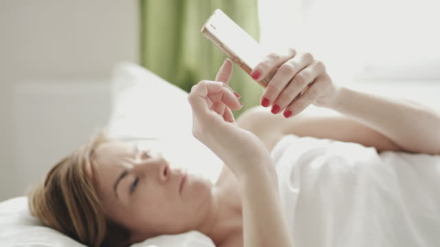 DS Woman using a mobile phone in bed Dolly shot of a mid adult woman using a mobile phone while she lying in bed in the morning. Shoot in 8K resolution. mid adult women stock videos & royalty-free footage