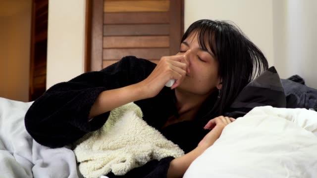 vídeos de stock, filmes e b-roll de mulher que usa um pulverizador nasal para desongest seu nariz - higiene