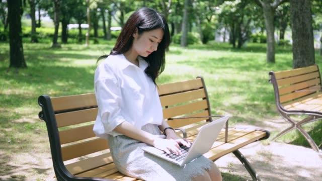 公園のベンチで pc を使用している女性 - パソコン 日本人点の映像素材/bロール