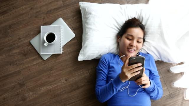 Mujer usando un teléfono inteligente caer en el suelo en su hogar con una taza de café y portátil, concepto de Música de sonidos - vídeo
