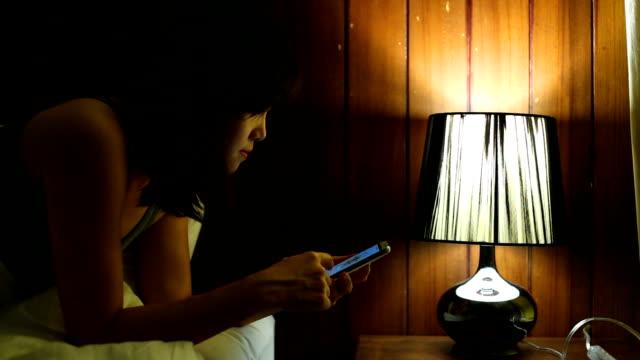 女性がベッドの上にスマート フォンを使用して - スマホ ベッド点の映像素材/bロール