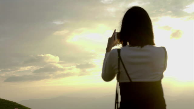4K: woman using a smartphone to take a sunset. video