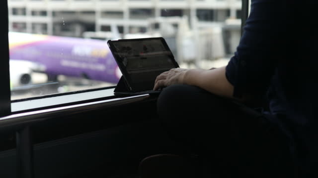 Woman using a tablet at the window in airport video