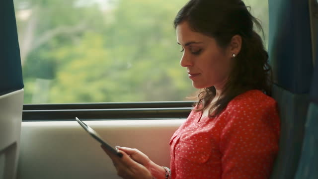 Woman using a tablet inside a moving train video