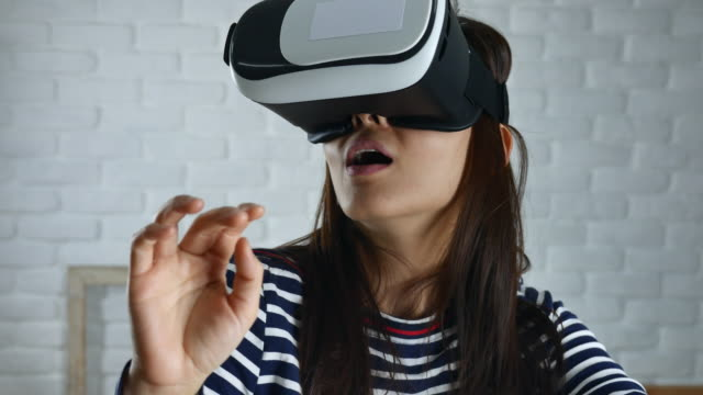 Woman using a virtual reality glasses at home video