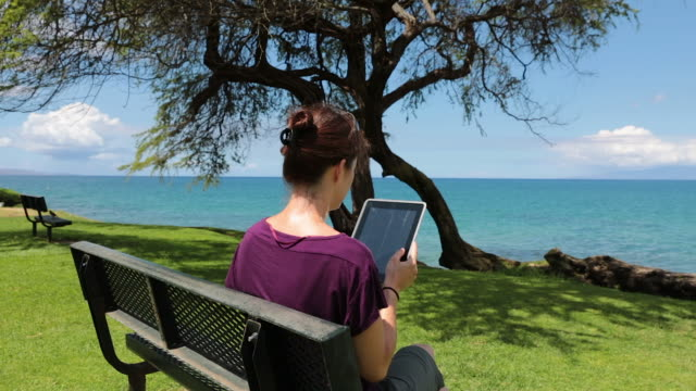 Woman Using an Electronic Tablet on a Bench at Beach, Hawaii
