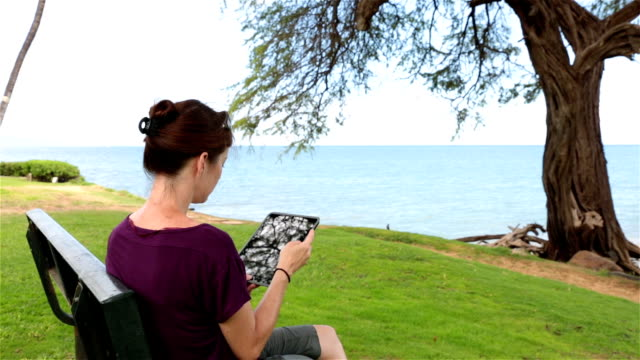 Woman using an electronic tablet on a bench DSLR video of a woman using an electronic tablet at the beach park, she is sitting on a bench close to the sea on a nice sunny day. She is reading, taking picture or selfie. pacific islands stock videos & royalty-free footage
